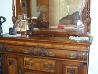 A British walnut back buffet, the moulded cornice above