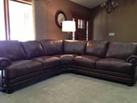 Gently utilized brown leather sectional sofa with