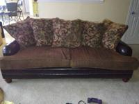 The couch has brown cushions and pillows with a leather