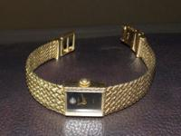 Gold plated bulova watch with one diamond in the. Black