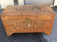 This is a cedar chest that is hand sculpted with