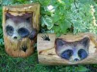 White pine carvings of spunky raccoons peeking thru