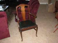 This is a nice old wooden arm chair with a leather seat