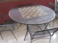 Round wrought iron table with a checker board in the