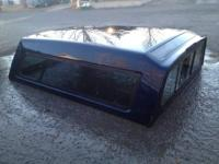 For sale is a dark blue camper shell or truck topper