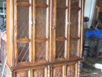 CHINA CABINET MADE OUT OF WOOD WITH LIGHT INSIDE.