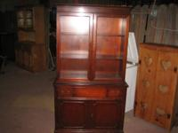 This is a previously used china cabinet with dark wood.