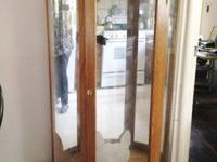 Curved glass cabinet with light fixtures, no shelves,