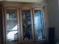 Lighted 2-door glass hutch sits on a buffet with 3