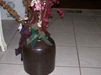 This clay pottery vase can hold many floral pieces or