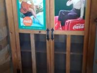 Two Coca Cola Girl Tin Signs framed to the door facing