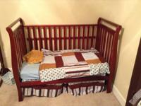 This is a cherry crib with mattress that converts to a