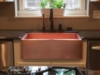 The copper sink and bronze fixtures are less than two