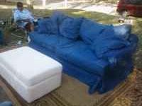 The couch is white with a blue cover the ottoman is the