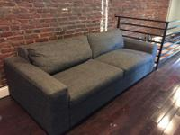 It's a grey couch that is 90 x 40 x 16. Two people can