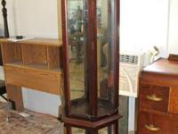 Curio cabinet has light at the top on the inside. Glass