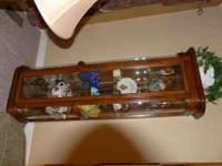 Lighted cherry curio cabinet with glass shelves.