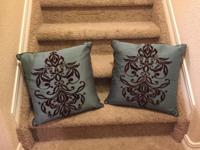 Stitched pattern on dark brown pillow, satin feel to