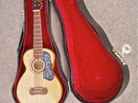 Mini, decorative acoustic guitar in case. Approximately