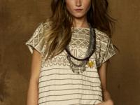 Allover patterned embroidery and knotted fringe add a