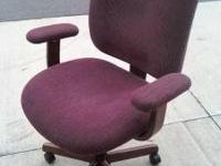 A desk chair with wood bottom, and garnet fabric. In