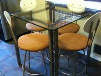 This is a glass top, bar-height, metal table with