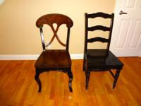 Two dining chairs made of wood in a rubbed black,