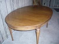 Solid wood round dining room table with claw feet.
