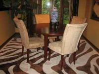 Round wood table with four chairs. Each chair is