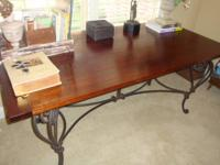 This is a dark wood table w/ a heavy rod iron frame and