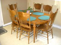 Wood dining table with 2 leaf extensions and 6 chairs.