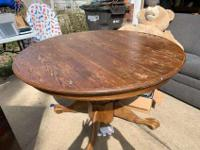 Round oak dining room table, seats 4. Has leaf that