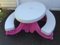 This is a cute picnic table with attached benches.