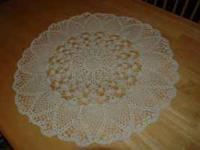"This doily is round, off white in color, 21 3/4"" and"