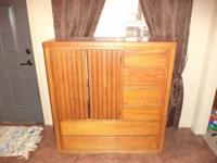 A wooden entertainment center with 4 small drawers and