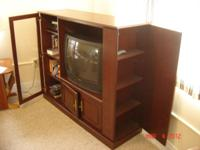 dark cherry paneled entertainment center holds a 30""