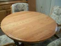 Round, blond wood dining room table, 4 chairs and one