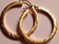 Real gold hollow hoop earrings with geometric etchings.