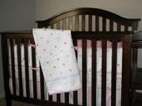 Nice dark wood baby crib , has a faded area in inside