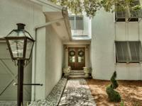 A shaded, cobblestone drive leads to a spectacular