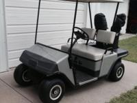EZ Go gas powered 4 wheel golf cart with top.