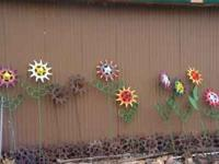 BEAUTIFUL FLOWERS MADE OUT OF OLD FARM EQUIPMENT PARTS.