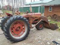 Farmall H tractor with wheel weights and chains