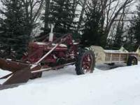 Farmall M and H tractors both with loaders trip