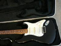 Black Fender Strat, with difficult shell case, tremolo