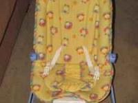 yellow and blue bouncy seat with birds on it. it is