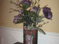Purple flowers displayed in decorative box with grape