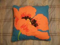 Bright blue throw pillow with orange and yellow flower