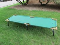 This is a green folding cot, wood and metal frame with