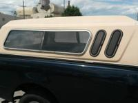 Up for sale is a tan colored long bed camper shell. I